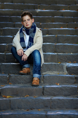 sad teenage boy sit on stone stairs outdoor Stock Photo