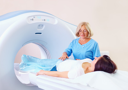 mid adult medical staff preparing patient to tomography photo