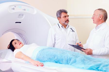 medical scanner: two doctors preparing patient to CT scanner procedure