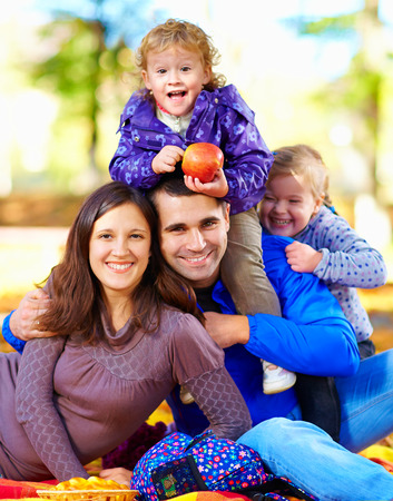 recreate: portrait of happy family in autumn park Stock Photo