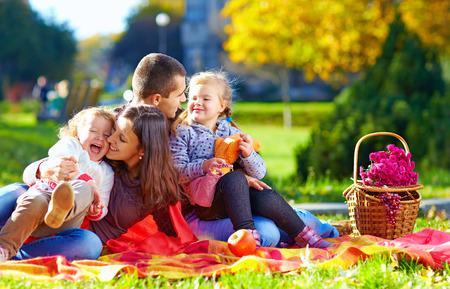 family picnic: familia feliz de picnic en el parque de otoño