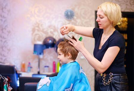 stylish women: little client, boy having haircut at hair salon