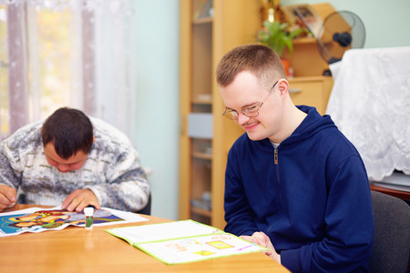 disable: young adult man engages in self study, in rehabilitation center Stock Photo