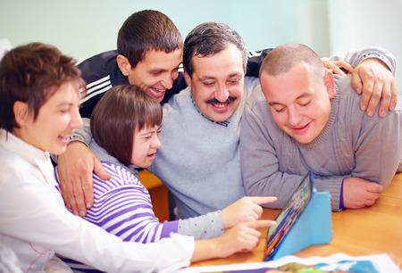 skupina šťastných lidí se zdravotním postižením, baví s tabletem Reklamní fotografie
