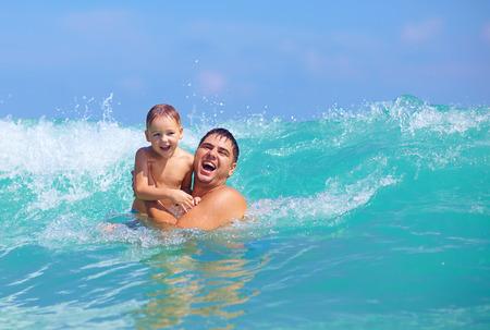 playa vacaciones: feliz padre e hijo se divierten en las ondas de agua Foto de archivo