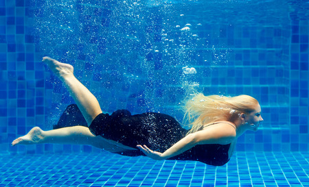 swimming to float: beautiful plus size woman diving in pool