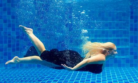 mooie plus size vrouw duiken in het zwembad