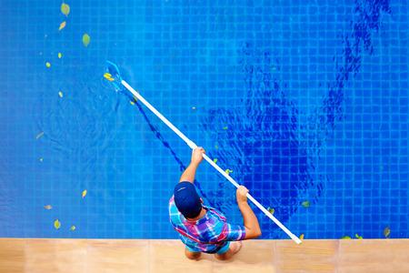 jong volwassen man, personeel het schoonmaken van het zwembad van bladeren