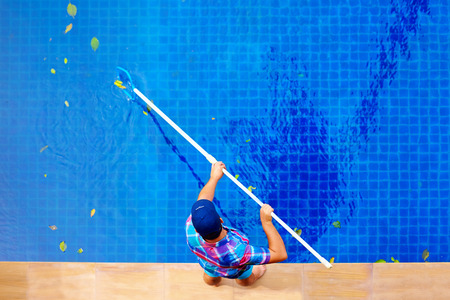 pool water: young adult man, personnel cleaning the pool from leaves Stock Photo