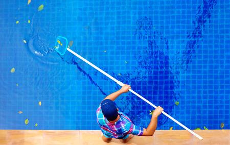 personal de limpieza: hombre adulto joven, el personal de limpieza de la piscina de las hojas Foto de archivo