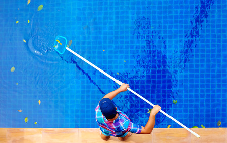 house cleaner: young adult man, personnel cleaning the pool from leaves Stock Photo