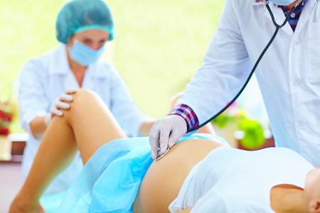 sala parto: medico ascolta il battito cardiaco del bambino durante il parto