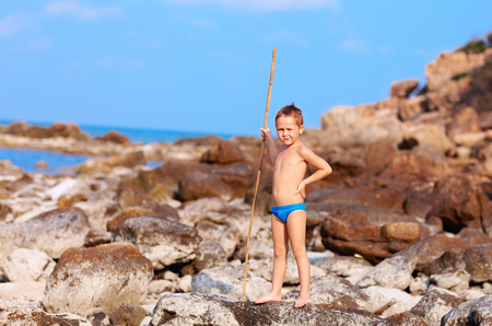 aborigine: cute boy with bamboo spear pretends like he is aborigine on desert island