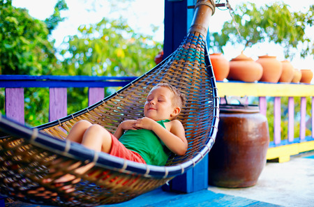 day bed: cute kid, boy relaxing in hammock. Enjoying life on tropical island