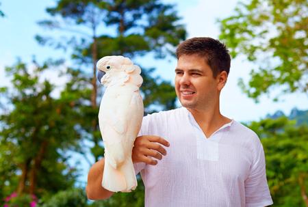 birdwatcher: young man, ornithologist holding gorgeous cockatoo parrot Stock Photo
