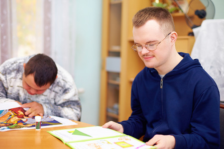 people with disabilities: young adult man engages in self study, in rehabilitation center Stock Photo