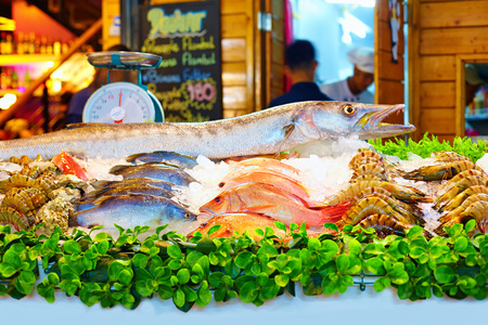 fish shop: variety of seafood on night market in Thailand