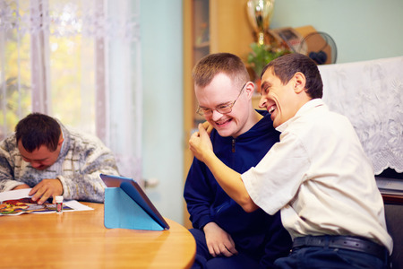 home care: happy friends with disability socializing through internet Stock Photo