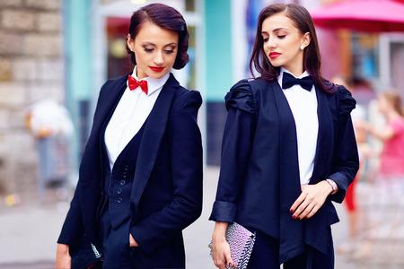 elegant woman: dos hermosas mujeres posando en traje negro