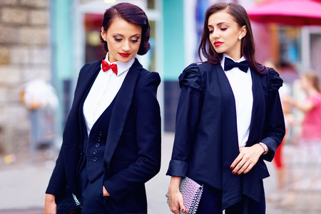 two gorgeous women posing in black suits