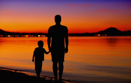 father and son near the water edge at sunset