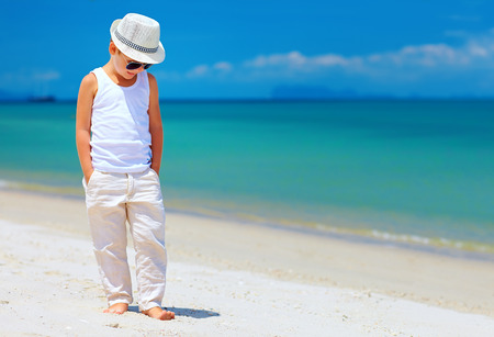 young style: stylish kid boy walking on the tropical beach