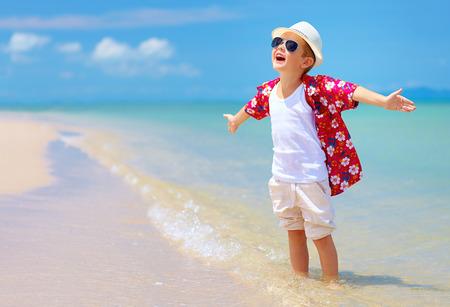 幸せなスタイリッシュな少年は夏のビーチでの生活を楽しんでいます
