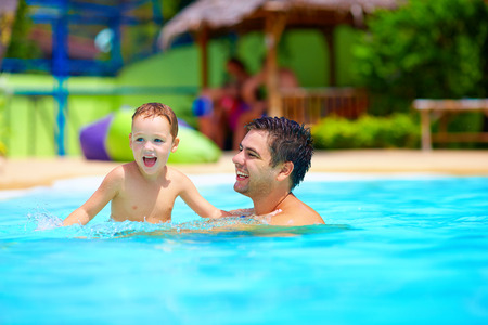 aqua park: father and son having fun in pool, summer vacation
