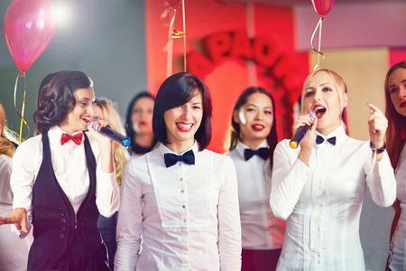 lazo negro: mujeres bonitas que se divierten en la fiesta de karaoke