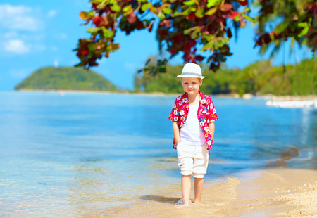 child model: cute kid boy walking in water on tropical beach