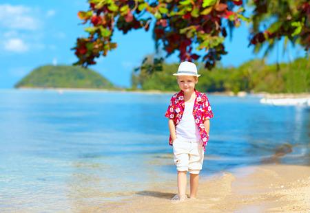 ni�o modelo: lindo chico ni�o caminando en el agua en la playa tropical