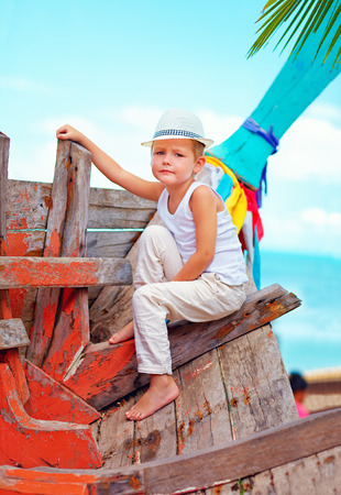 cute kid, boy sitting on old boat on tropical beach photo