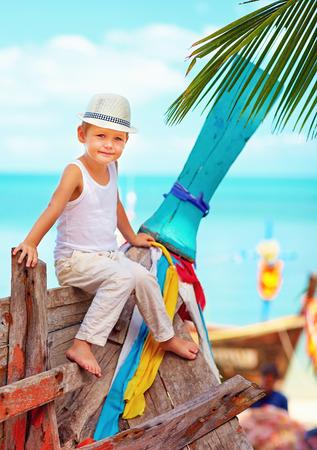 tropical beach: cute kid, boy sitting on old boat on tropical beach