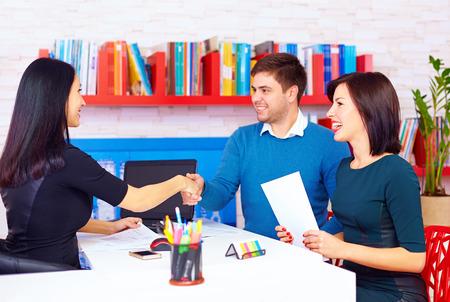 満足しているクライアントは、オフィスで成功するビジネスの交渉の後のカップル