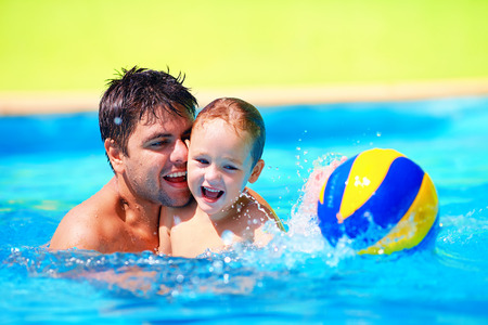 happy family playing in water polo in the pool
