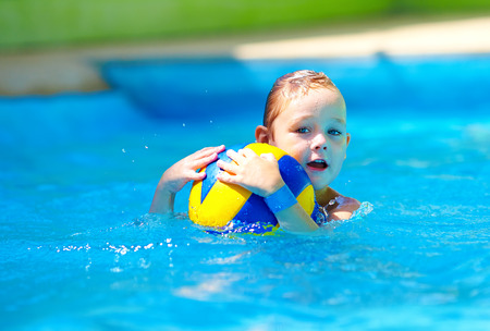 recreate: cute kid playing water sport games in pool