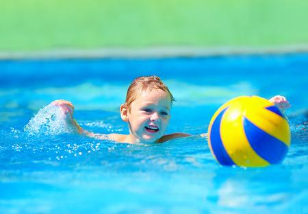 waterpolo: lindo niño jugando juegos de deportes acuáticos en la piscina