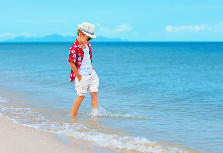 young feet: fashionable boy, kid playing in waves on summer beach