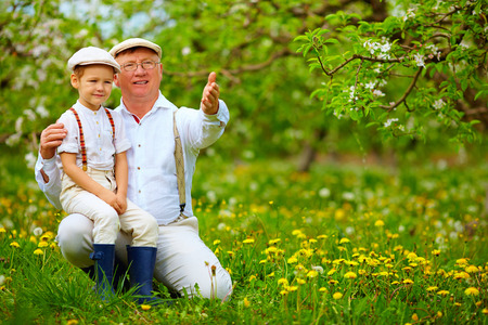grandfather sharing experience with grandson in spring garden Banco de Imagens