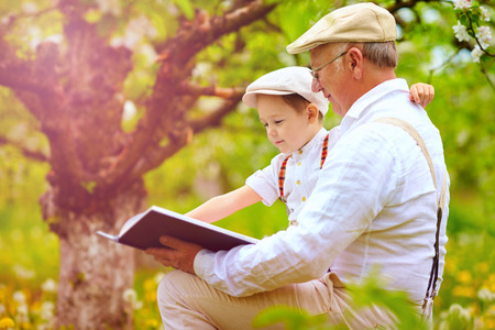 grandfather with grandson reading book in spring garden Archivio Fotografico