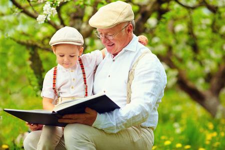 lifestyle: Großvater mit Enkel liest ein Buch im Frühjahr Garten