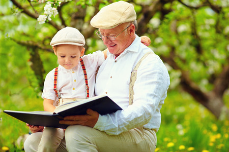 grandfather with grandson reading book in spring garden Stockfoto