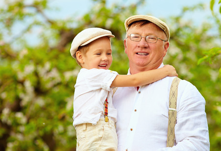 grand father: Cute grandpa with grandson on hands in spring garden Stock Photo