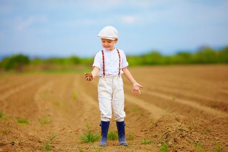 clod: Cute little farmer on spring field  holding earth clod