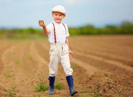 Pequeño granjero lindo en el campo de primavera celebración tierra terrón Foto de archivo - 39722144