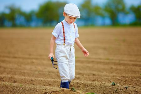 Lindo agricultor niño caminando el campo de cultivo Foto de archivo - 39720603