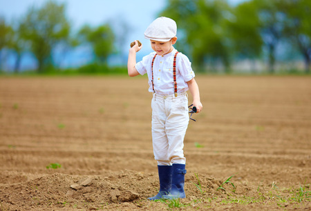 clod: Cute little farmer on spring field, with earth clod in hand