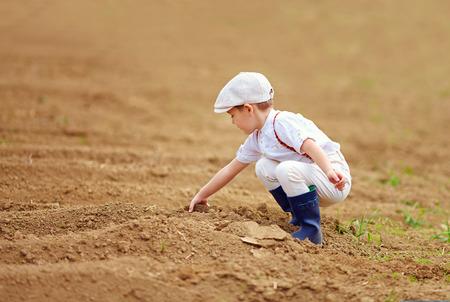 farm boys: Cute little farmer spuding the soil on spring field