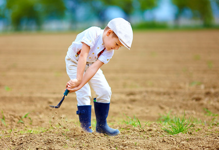 spud: Cute little farmer working with spud on spring field Stock Photo