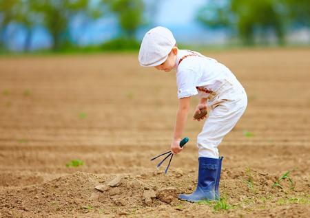 Pequeño granjero lindo trabajar con spud en campo de primavera Foto de archivo - 39684238